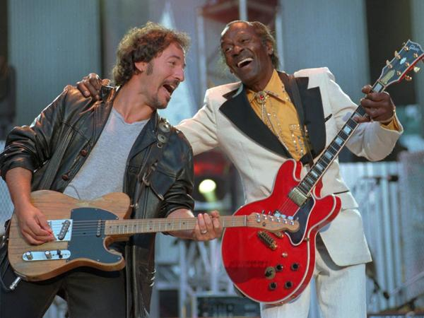 """In this Sept. 2, 1995 file photo, Bruce Springsteen, left , and Chuck Berry laugh as they perform the Berry hit """"Johnny B. Goode"""" at the Concert for the Rock and Roll Hall of Fame in Cleveland. Berry was the opening act of the concert."""