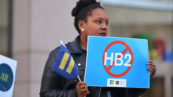 Cassandra Thomas of Human Rights Campaign holds a sign advocating the repeal of HB2 on Dec. 7, 2016, in Charlotte.
