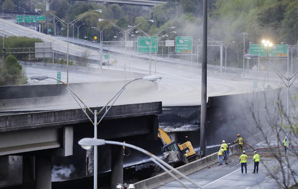 Crews inspect a section of an I-85 overpass in Atlanta that collapsed from a large fire, roiling traffic in the heart of the city. Officials have completely shut down the heavily traveled road.