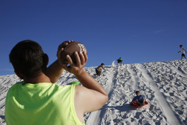Families play on the dunes. At White Sands, dune sledding is encouraged — they even sell plastic flying saucers in the gift shop.