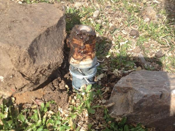 """An M-44 — also known as a """"cyanide bomb"""" for the way it sprays sodium cyanide — sits nested between two rocks. Mark Mansfield, father of a boy accidentally sprayed March 16 in Idaho, calls these devices used to protect livestock from predators """"neither safe nor humane."""""""