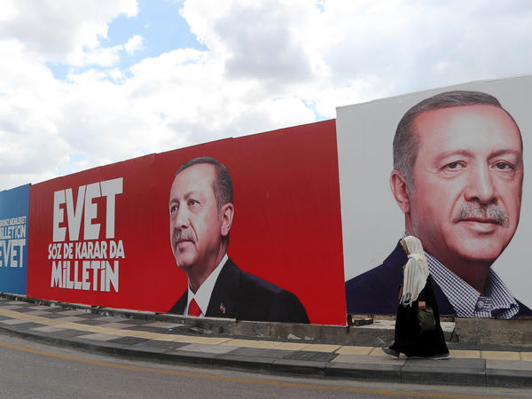 A woman walks past a giant poster bearing portraits of Turkish President Recep Tayyip Erdogan in Ankara, ahead of the referendum on whether to change the current parliamentary system into an executive presidency.