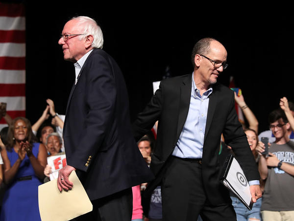 """Sen. Bernie Sanders and Democratic National Committee Chair Tom Perez walk past each other during their """"Come Together and Fight Back"""" tour at the James L. Knight Center on Wednesday in Miami, Fla."""