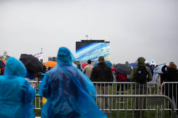 People gather to watch a presentation during the rally near the Washington Monument.