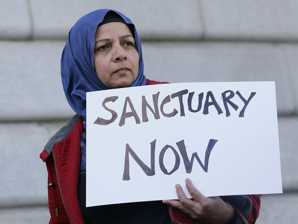 Protester Moina Shaiq holds a sign at a rally outside City Hall in San Francisco. On Tuesday, a federal judge blocked a Trump administration order to withhold funding from sanctuary communities.