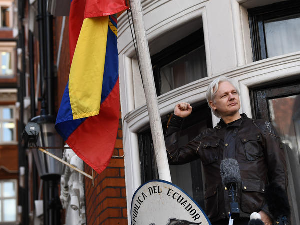 """WikiLeaks founder Julian Assange raises his fist before addressing reporters from the balcony of the Ecuadorian Embassy in London on Friday. In his speech, Assange said there are still plenty of legal battles still to wage: """"The proper war is just commencing."""""""