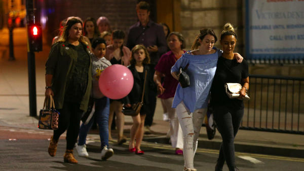 People leave Manchester Arena in England on Monday night following an explosion that killed at least 22 victims and wounded dozens more.