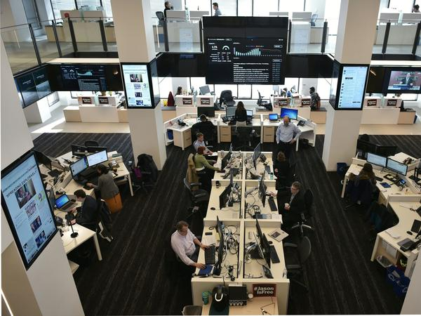 Journalists at <em>The Washington Post</em> work in a newsroom surrounded by screens showing its website and updated reader metrics.
