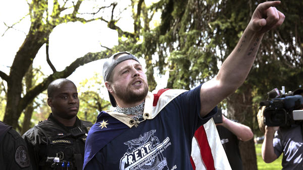 "Jeremy Christian (right), seen during a Patriot Prayer, allegedly stabbed three men, two fatally, in Portland earlier this year. During a subsequent courtroom appearance, he exclaimed: ""Free speech or die, Portland. You call it terrorism I call it patriotism."""