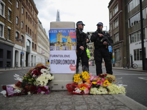 Police stand guard behind flowers left in memorial on Southwark Street near the scene of Saturday's terror attack in London.