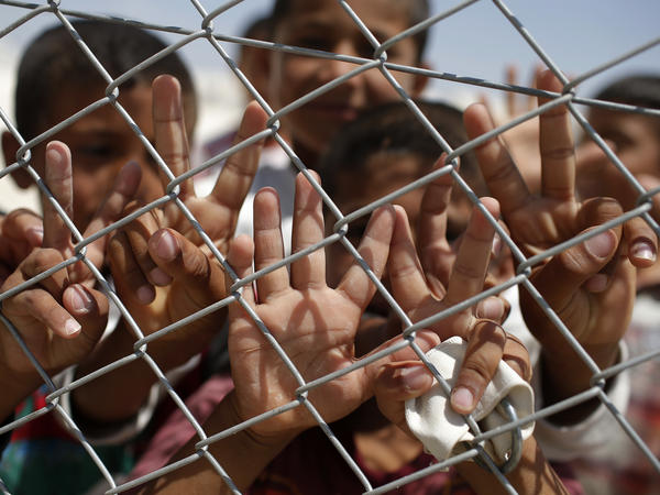 Syrian refugee children flash the V-sign at a camp in Suruc, a Turkish city near the border with Syria.