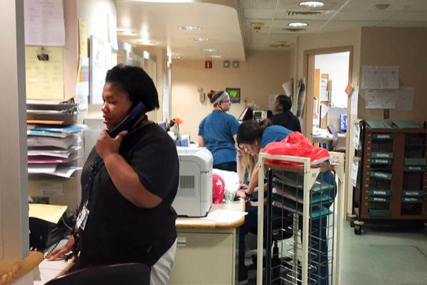 Nurses at the telemetry unit of Trinity Hospital respond to patient calls and monitor patient vital signs.