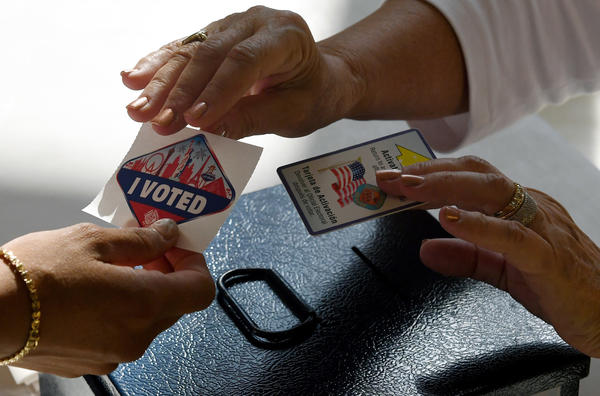 """A poll worker hands out a Las Vegas Strip-themed """"I Voted"""" sticker after taking back her voter activation card on Nov. 8, 2016, in Nevada. A White House panel that is looking into voter fraud allegations wants names, addresses, birthdates, party affiliation and elections voted in since 2006 for every registered voter in the country."""