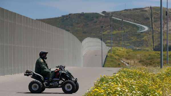 A Border Patrol agent keeps watch over the U.S.-Mexico border fence just south of San Diego earlier this year. The Department of Homeland Security announced Tuesday that it would waive environmental and other laws to expedite its construction of barriers and roads in the region.