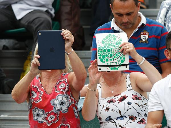 A spectator at Wimbledon last month uses an iPad to take pictures of the action. Improved sales of the tablets were part of the good news out of Apple's quarterly report.