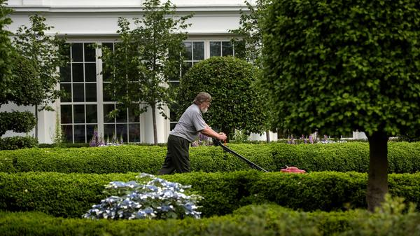 A groundskeeper cuts grass near the East Wing of the White House on May 31, 2016.