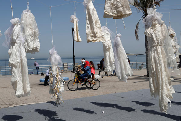 A veiled woman rides a bicycle with a child past white wedding dresses displayed as a desecrated symbol by the Lebanese nongovernmental organization Abaad. The group is part of an effort against article 522 in Lebanon's penal code, which stipulates that a rapist is absolved of his crime if he marries his victim.