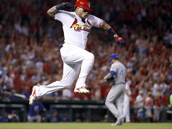 St. Louis Cardinals' Yadier Molina, left, celebrates after hitting a grand slam off Kansas City Royals relief pitcher Peter Moylan during the sixth inning of a baseball game Wednesday, Aug. 9, 2017, in St. Louis.