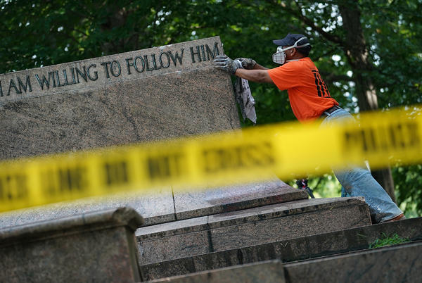 """Baltimore city workers remove graffiti from the pedestal where a statue dedicated to Robert E. Lee and Thomas """"Stonewall"""" Jackson stood on Wednesday. The City of Baltimore removed four statues celebrating confederate heroes from city parks overnight, following the weekend's violence in Charlottesville, Va."""