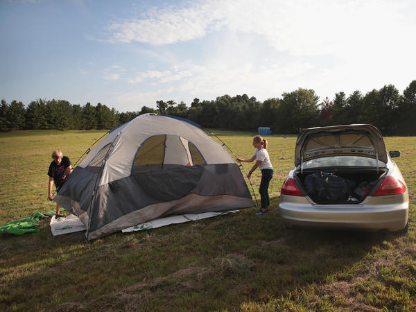 Karen Just and her son Mathew pitch a tent in a hay field which had been converted into a campground to host visitors for Monday's solar eclipse near Carbondale, Ill. All of the commercial lodging and hotels in the area are completely booked.