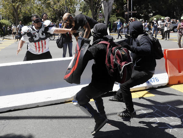 Patriot Prayer founder Joey Gibson (second from left) is chased by anti-fascists during a Rally Against Hate on Sunday in Berkeley, Calif.