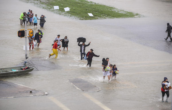 People walk down a flooded street as they evacuate their homes in Houston on Monday.
