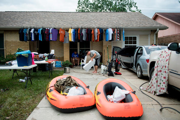 A man cleans his belongings after flood waters receded during the aftermath of Hurricane Harvey in Houston, Texas.