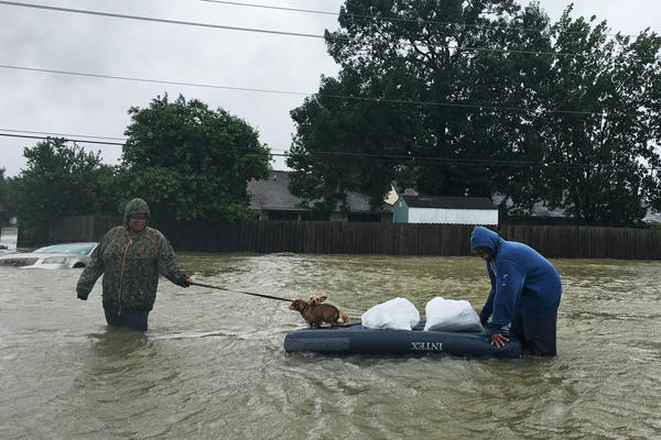 Amber and Curtis Fletcher evacuate their neighborhood with their dogs in northeast Houston, using an inflatable twin mattress they had at their house.