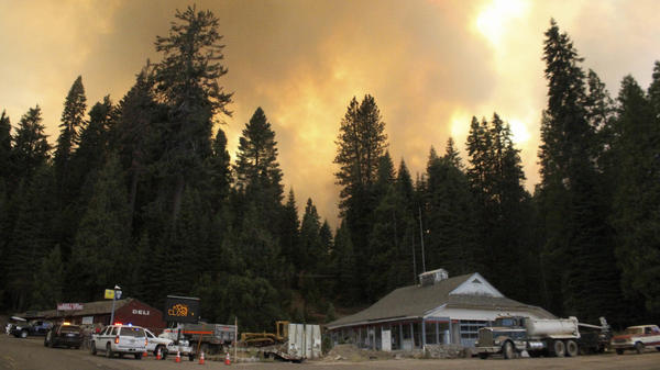 Smoke rises from a wildfire behind the Fish Camp General Store near Yosemite National Park in Fish Camp, Calif., last week. The wildfire is among many burning across the Western U.S.