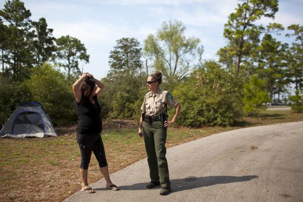Susan Arawley (left) speaks with Jamie Creacy, superintendent of the Lost Pines Complex, which includes Bastrop State Park. As Hurricane Harvey hit, Arawley tried picking up supplies and got stuck in rising flood water. After sleeping in her car four nights, she decided to head to Bastrop State Park, where she could take a shower.
