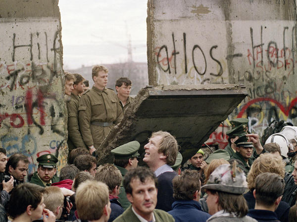 West Berliners crowd in front of the Berlin Wall on Nov. 11, 1989, as they watch East German border guards demolishing a section of the wall in order to open a new crossing point between East and West Berlin.