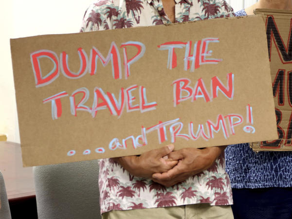 A demonstrator holds a sign protesting the travel ban in Honolulu in June. The 9th Circuit Court of Appeals on Thursday sued the latest ruling against the Trump administration's order.