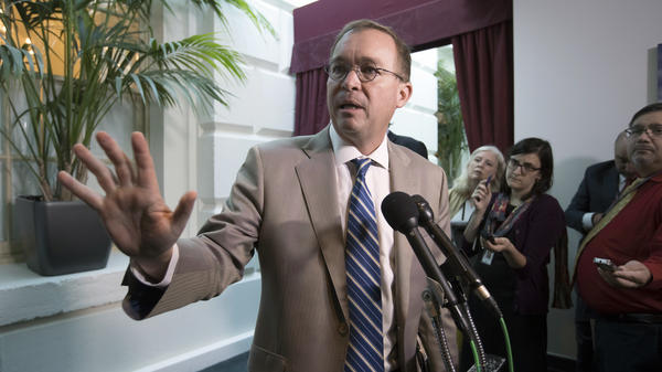 White House Budget Director Mick Mulvaney leaves a Republican strategy session in which he and Treasury Secretary Steven Mnuchin were blasted by lawmakers over President Trump's deal with Democrats.