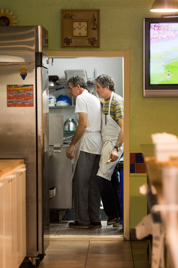 Café Croissant owners and twin brothers Didier (left) and Pascal Vedel prepare food in their kitchen. This is the strongest storm they have experienced while living in Miami.