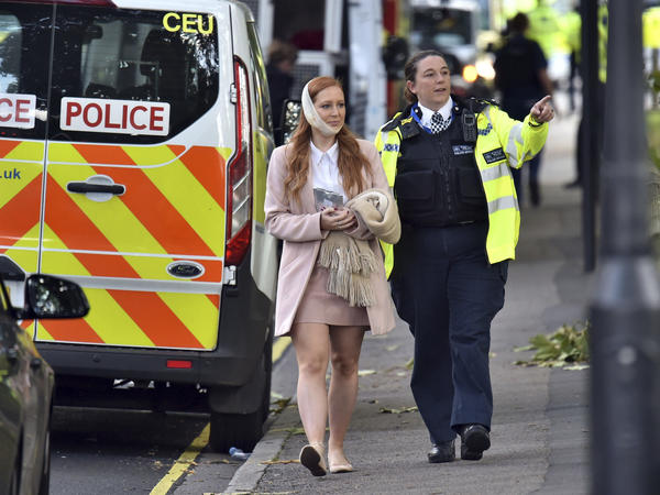 An injured woman is assisted by a police officer close to Parsons Green station in west London after Friday's explosion on a packed subway train was declared a terrorist incident.
