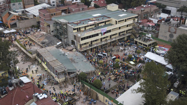 The collapsed section of the Enrique Rebsamen school in Mexico City is surrounded by volunteers and rescue workers on Wednesday. A wing of the three-story building collapsed into a massive pancake of concrete slabs during Mexico's deadliest earthquake in years.