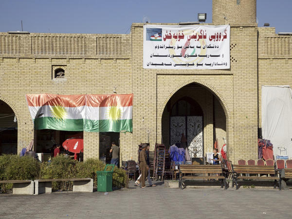 A campaign poster next to a Kurdish flag in Irbil urges people to vote yes Monday on independence from Iraq.