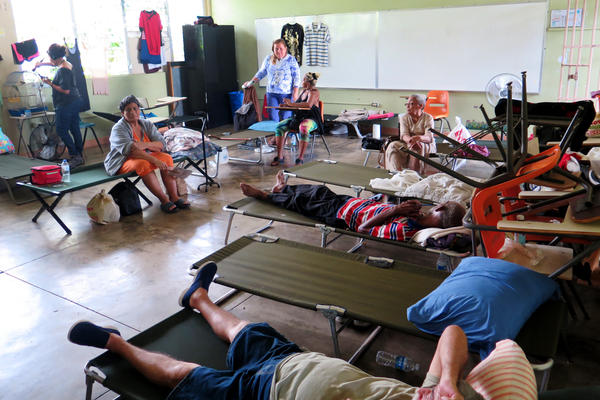 Carmen Rivera (at left in the orange dress) sits on a cot at the Cataño shelter. She suffers from severe asthma and knee pain and has had to be rushed by ambulance to the hospital for asthma treatment twice since the hurricane. She says she feels forgotten by authorities.