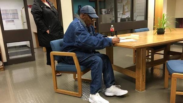 O.J. Simpson signs papers as he prepares to leave prison in Nevada.