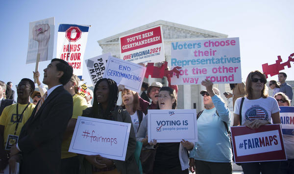 Demonstrators protest outside the Supreme Court on Tuesday as the court hears arguments about partisan gerrymandering.
