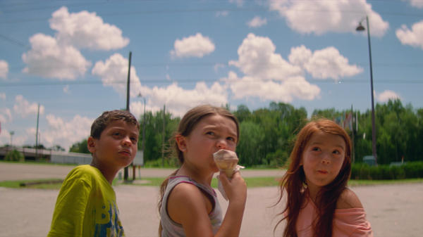 Six-year-old Moonee (Brooklynn Prince, center) and her buddies Scooty (Christopher Rivera, left) and Jancey (Valeria Cotto) run wild around her motel home in <em>The Florida Project</em>.