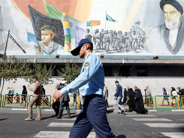 A member of the Iranian army walks past a mural in Tehran depicting the late Iranian Supreme Leader Ayatollah Ruhollah Khomeini (right), on Friday.