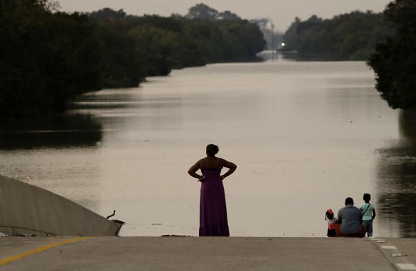 Filled to the brim by Hurricane Harvey's rainwaters, the Addicks and Barker reservoirs are finally empty once again. In this photo from Sept. 1, days after the hurricane first made landfall, a family looks at floodwaters in the Addicks Reservoir from a closed freeway.