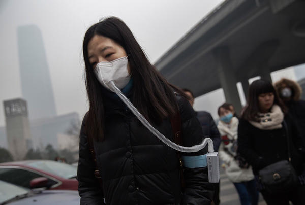 A woman wears a mask and filter as she walks to work during heavy pollution in Beijing, China.