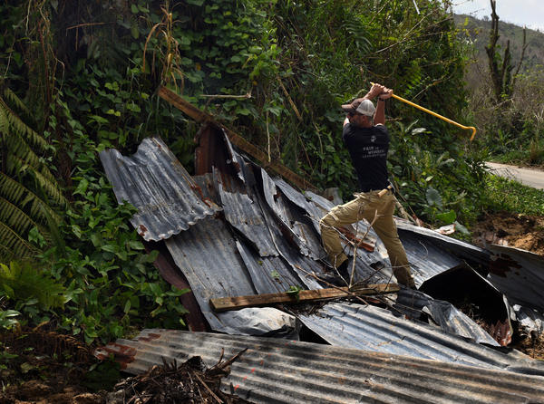 Daniel Braithwaite, a volunteer from Florida who is traveling with troops, gathers materials to repair Ruben Caraballos' leaking roof in Utuado.
