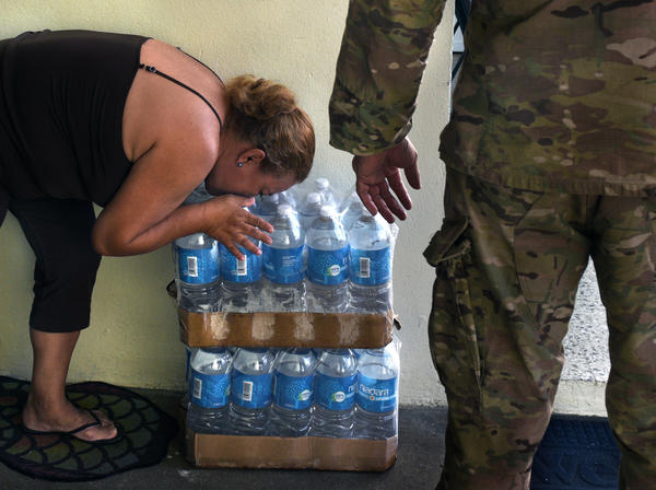 "Iris Camacho, of Aibonito, kisses cases of water left by Santini. ""Water is like gold around here,"" he said."