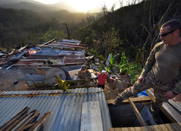 Santini (right) and <strong></strong>Sgt. Kenneth<strong> </strong>McAnally with troops and volunteers from the Crisis Relief Team repair Ruben Caraballos' leaking roof in Utuado.