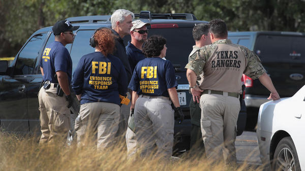 Law enforcement officials continue their investigation at the First Baptist Church of Sutherland Springs in Texas on Monday.