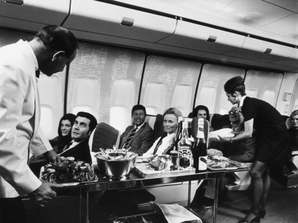 A steward and stewardess serving first-class passengers with drinks and refreshments on board a Boeing 747 in 1970.