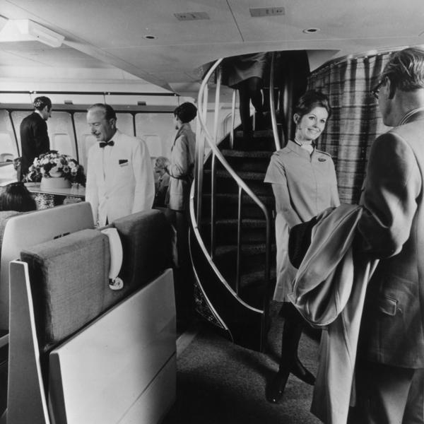 In 1970, an air hostess greets a passenger in front of a spiral staircase on a Boeing 747, which leads to the upper deck lounge.